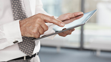 Close up of businessman's hands touching digital tablet --- Image by © John Smith/Corbis